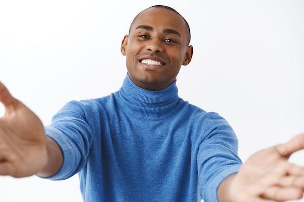 Ritratto ravvicinato di un uomo afroamericano bello, adorabile e dall'aspetto amichevole che allunga le mani in avanti per abbracciarlo, coccolarlo