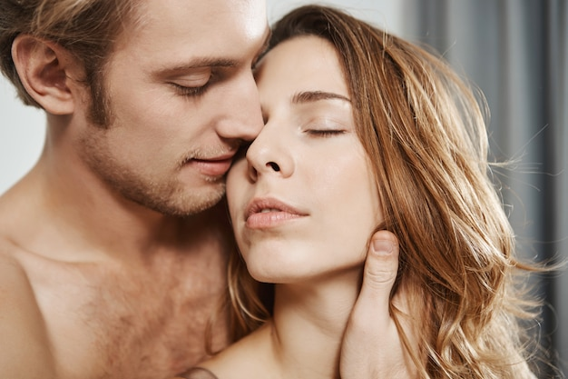 Close-up portrait of handsome loving boyfriend holding woman behind while being in bedroom. couple enjoys every time they spend together, feeling relaxed and happy to finally found soulmate.