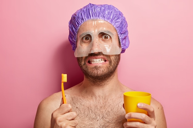 Close up portrait of handsome man holds toothbrush and yellow cup, stands with bare shouders, has mask on face