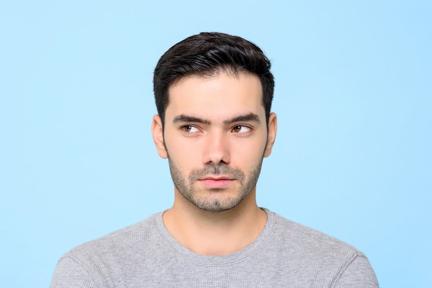 Close up portrait of handsome man thinking with eyes looking sideways isolated