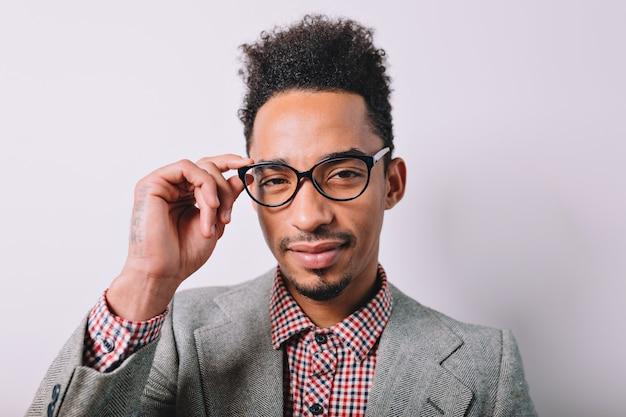 Ritratto del primo piano del bel ragazzo nero moderno indossa occhiali alla moda e abito grigio che tiene gli occhiali su grigio