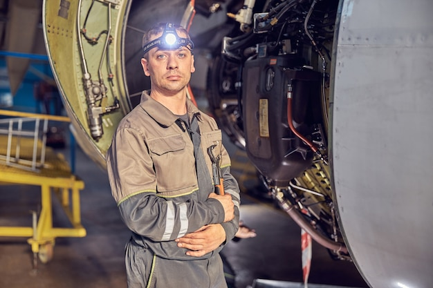 Close up portrait of handsome responsible aviation mechanic standing with keeping arms crossed in front of open engine in the aerodrome