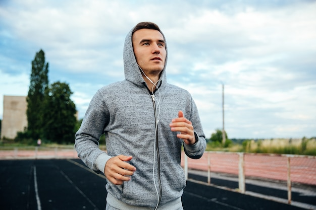 Close-up portrait of a handsome running sportsman, wearing sweatshirt with hood