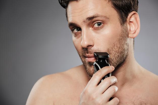 Close up portrait of a handsome shirtless man shaving beard