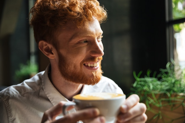 Close-up portrait of handsome smiling redhead bearded man, holding coffee cup, looking aside