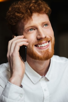 Close-up portrait of handsome smiling redhead bearded man in white shirt tolking on mobile phone