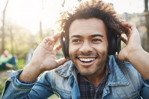 Close-up portrait of handsome unshaved dark-skinned guy holding hands on headphones while listening music and being excited, looking aside, sitting in park.