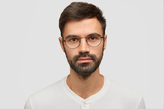 Close up portrait of handsome unshaven man with thick beard and mustache, has dark hair, looks seriously
