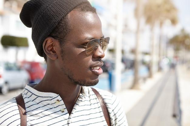 Close-up portrait of handsome young african american male student in stylish shades and headwear having nice walk in foreign city in hot sunny morning while spending his summer vacations abroad