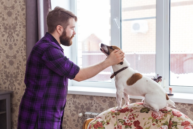 Close up portrait handsome young hipster man plays and loves his good friend dog at home. positive human emotions, facial expression, feelings.