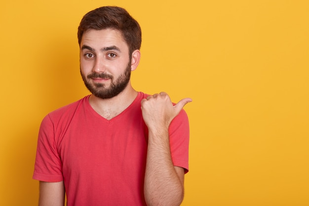 Close up portrait of handsome young male with beard pointing aside with thumb