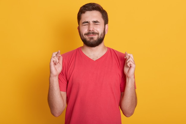 Close up portrait of handsome young man wearing red t shirt keeping eyes closed and fingers crossed