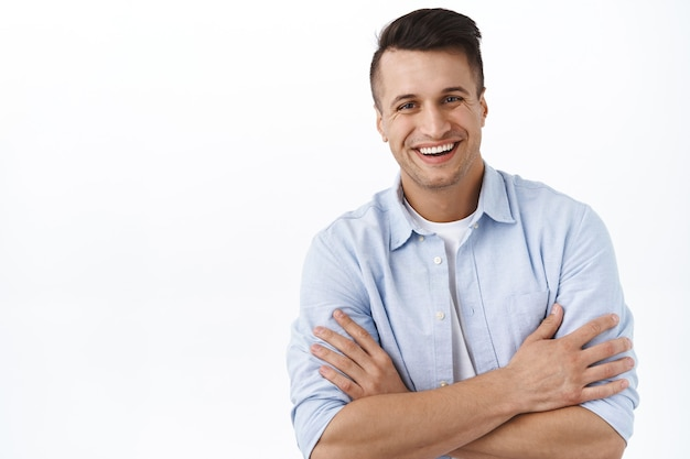 Close-up portrait of handsome young professional male employee, businessman with satisfied grin, cross arms chest confident pose  beaming smile, white wall