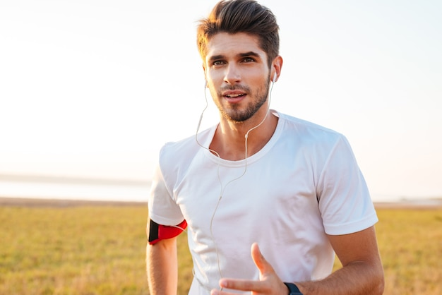 Close up portrait of a handsome young sportsman running outdoors and listening to music with earphones