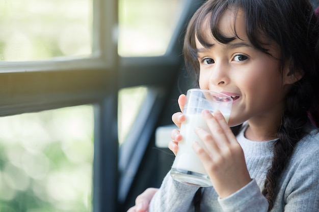 Close up portrait of happy adorable girl holding glass with milk looking away