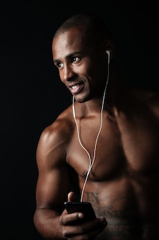 Close-up portrait of happy afro american sports man holding phone in hand while listen to music