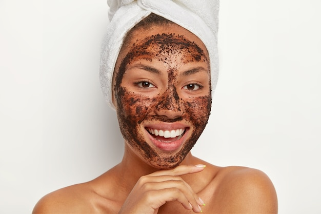 Close up portrait of happy afro woman touches chin gently, smiles broadly, shows white teeth, cleans face, applies coffee scrub mask, wears wrapped towel on wet hair after taking bath. skin care