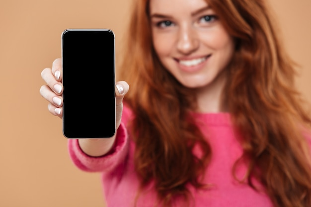 Close up portrait of a happy attractive redhead girl showing smartphone