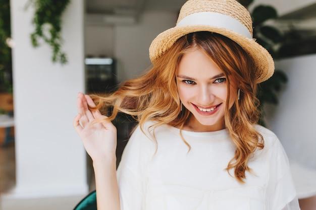 Ritratto del primo piano della ragazza felice dagli occhi azzurri che gioca con i capelli ricci