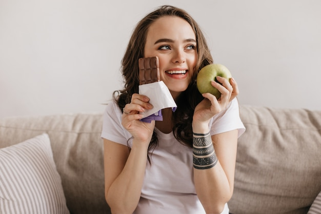 Close-up portrait of happy brunette young woman holding green apple and sweet milk chocolate