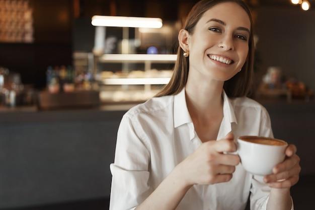 カフェに座っているように元気に笑って、白いブラウスでクローズアップの肖像画の幸せな実業家。