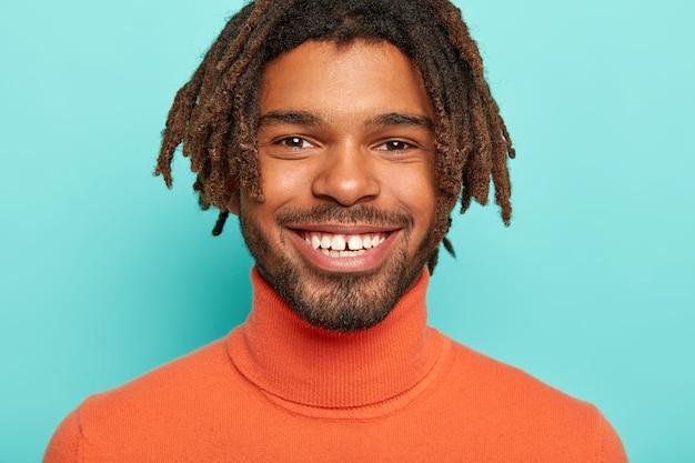 Close up ritratto di felice uomo spensierato ha un sorriso a trentadue denti, mostra denti bianchi perfetti, guarda volentieri