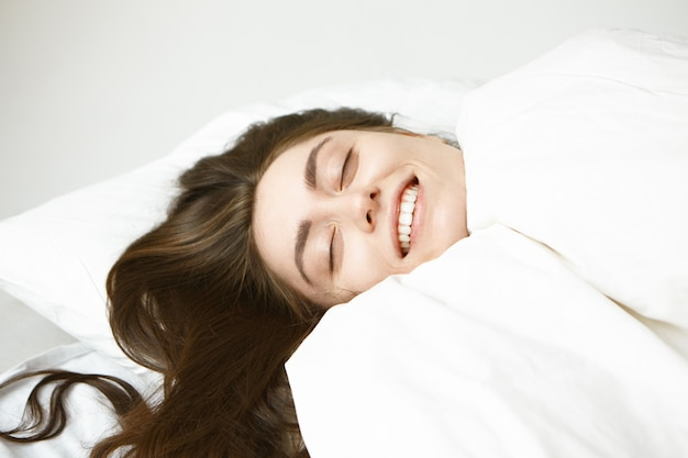 Close up portrait of happy carefree young caucasian woman with shiny brunette hair closing eyes with pleasure, relaxing in bed wrapped in white blanket, feeling warm and comfortable on cold winter day