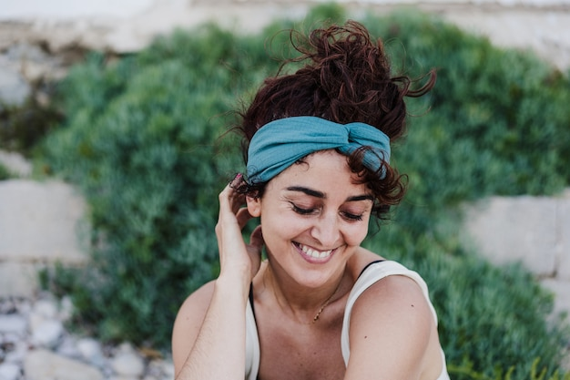 Close up portrait of happy caucasian woman smiling in front of green vegetation during summer time. outdoors lifestyle