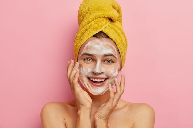 Close up ritratto di felice donna caucasica lava il viso con acqua e sapone per il viso, vuole avere una carnagione sana, rimuove lo sporco e il sudore sebo, asciugamano avvolto giallo sulla testa