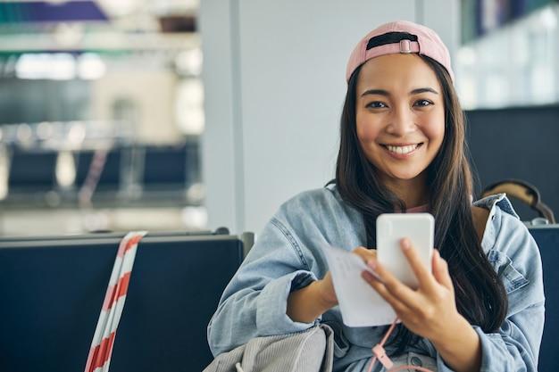 실내에서 사진 카메라를보고 포즈를 취하는 손에 휴대 전화로 초상화 행복 쾌활한 여자를 닫습니다
