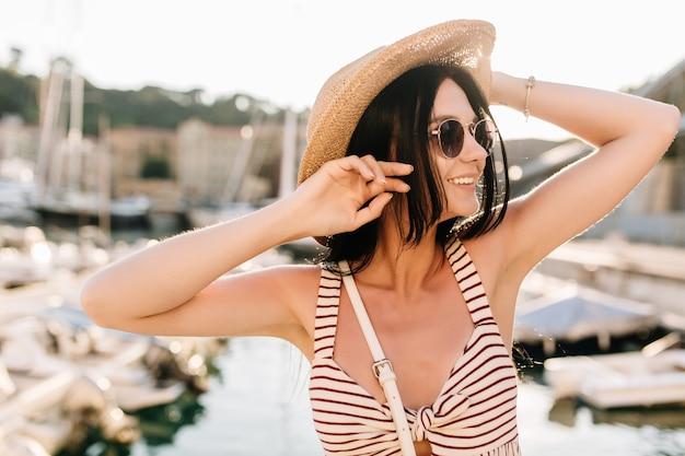 Ritratto del primo piano della ragazza dai capelli scuri felice in cappello ed elegante braccialetto che guarda lontano con un sorriso carino nella mattina di sole