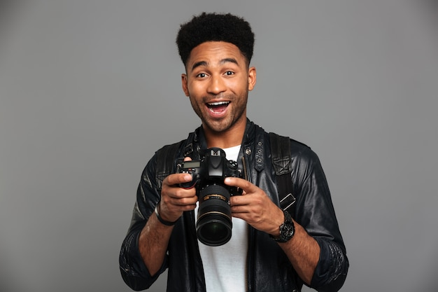 Close-up portrait of happy exited afro american man holding photocamera