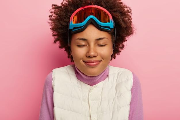 Close up ritratto di felice sciatore femminile pone in maglia bianca, occhiali da snowboard, ha l'acconciatura riccia