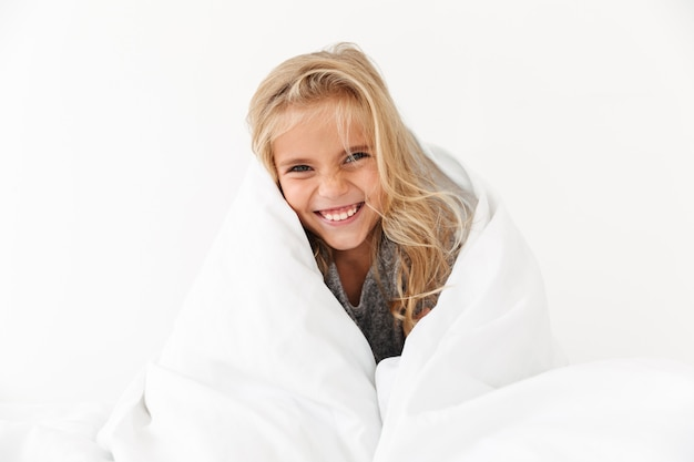 Close-up portrait of happy girl covering with white blanket,