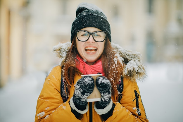 Close up portrait of happy girl in frosty winter city. flying snowflakes