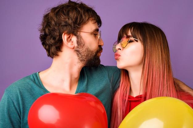 Chiuda sul ritratto delle coppie felici dei pantaloni a vita bassa che guardano l'un l'altro e provano a baciare, che tengono palloncini, vestiti casual alla moda luminosi e occhiali, atmosfera romantica