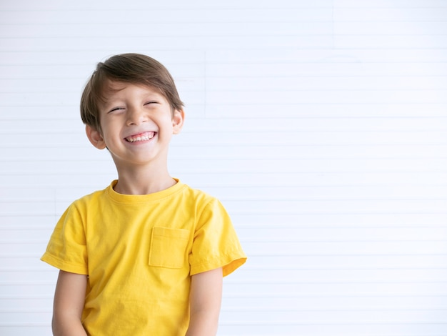 Close up portrait of a happy little boy smiling on white background