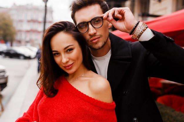 Close up ritratto di felice bella donna bruna e bell'uomo con gli occhiali. all'aperto. bella coppia innamorata in posa sul manzo durante le vacanze.