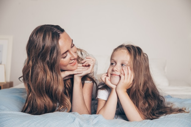 Close up portrait of happy loving family lying relaxing enjoying in bedroom together. mother and her cute preschool daughter child girl in pajamas lying in bed.