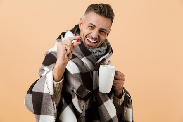 Close up portrait of a happy man wrapped in a blanket standing isolated over beige wall, showing pill capsule