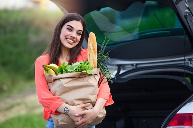 Close up portrait of a happy pretty girl holding bag with groceries and looking at camera with copy space. close up of a woman holding heavy bag with groceries.