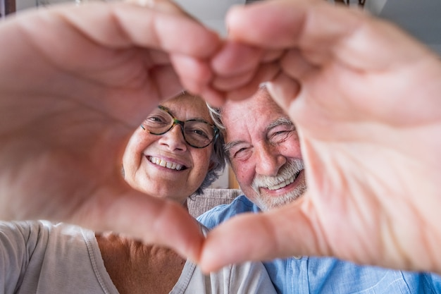 Close up portrait happy sincere middle aged elderly retired family couple making heart gesture with fingers, showing love or demonstrating sincere feelings together indoors, looking at camera.