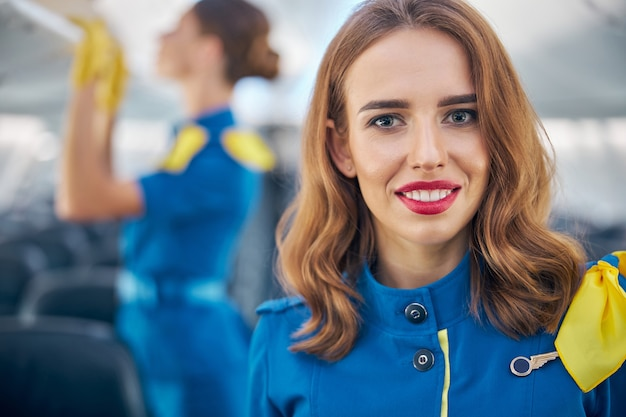 Close up portrait of happy smiling red hair flight attendant looking at the photo camera while standing in front of another air hostess