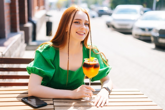 Close-up portrait of happy smiling young woman drinking cocktail through straw sitting at table in outdoor cafe in sunny summer day. beautiful female student drinking cool lemonade through straw.