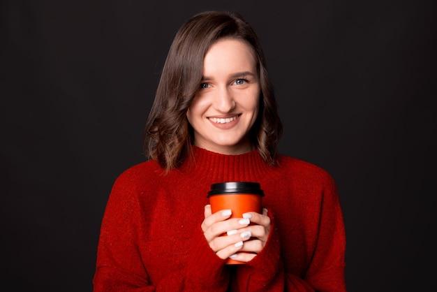 行くためにコーヒーのカップを保持し、カメラを見ている肖像画の幸せな女性をクローズアップ
