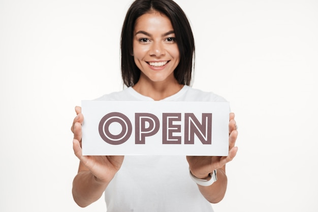 Close up portrait of a happy woman holding open sign