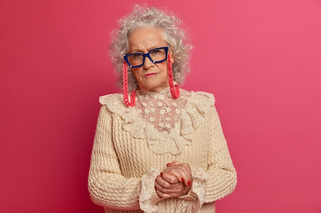 Close up portrait of happy wrinkled fashionable granny wearing glasses and sweater