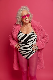 Close up portrait of happy wrinkled fashionable granny wearing pink tights and coat