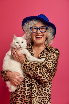 Close up portrait of happy wrinkled fashionable granny with beautiful cat