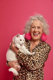Chiuda sul ritratto della nonna alla moda rugosa felice con il bellissimo gatto